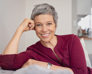 Mature Woman with Bright White Smile Sitting on Couch