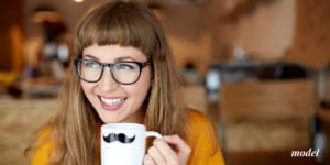 Smiling Model with Glasses Holding Mug With a Mustache